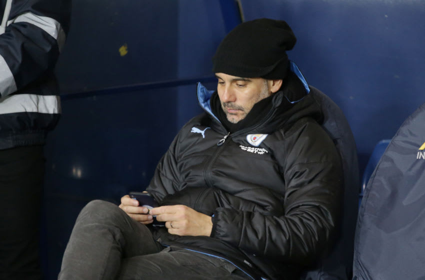 OXFORD, ENGLAND - DECEMBER 18: Pep Guardiola of Manchester City checks his mobile phone before during the Carabao Cup Quarter Final match between Oxford United and Manchester City at Kassam Stadium on December 18, 2019 in Oxford, England. (Photo by Robin Jones/Getty Images)