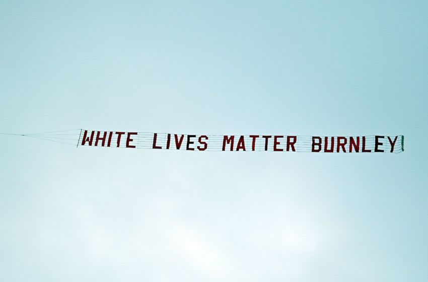 A banner reading 'White Lives Matter Burnley' is towed by a plane above the stadium during the English Premier League football match between Manchester City and Burnley at the Etihad Stadium in Manchester, north west England, on June 22, 2020. (Photo by Shaun Botterill / POOL / AFP) / RESTRICTED TO EDITORIAL USE. No use with unauthorized audio, video, data, fixture lists, club/league logos or 'live' services. Online in-match use limited to 120 images. An additional 40 images may be used in extra time. No video emulation. Social media in-match use limited to 120 images. An additional 40 images may be used in extra time. No use in betting publications, games or single club/league/player publications. / (Photo by SHAUN BOTTERILL/POOL/AFP via Getty Images)