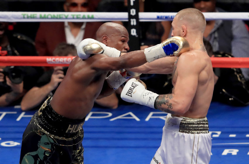 LAS VEGAS, NV - AUGUST 26: (L-R) Floyd Mayweather Jr. throws a punch at Conor McGregor during their super welterweight boxing match on August 26, 2017 at T-Mobile Arena in Las Vegas, Nevada. (Photo by Sean M. Haffey/Getty Images)