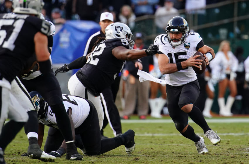 Gardner Minshew II of the Jacksonville Jaguars scrambles from P.J. Hall #92 of the Oakland Raiders. (Photo by Daniel Shirey/Getty Images)