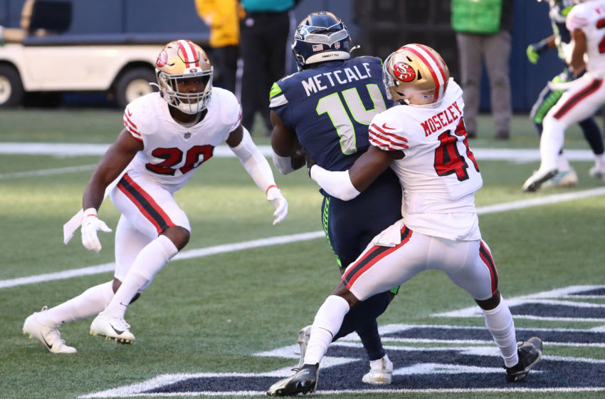 SEATTLE, WASHINGTON - NOVEMBER 01: DK Metcalf #14 of the Seattle Seahawks scores a touchdown against Emmanuel Moseley #41 and Jimmie Ward #20 of the San Francisco 49ers in the second quarter of the game at CenturyLink Field on November 01, 2020 in Seattle, Washington. (Photo by Abbie Parr/Getty Images)