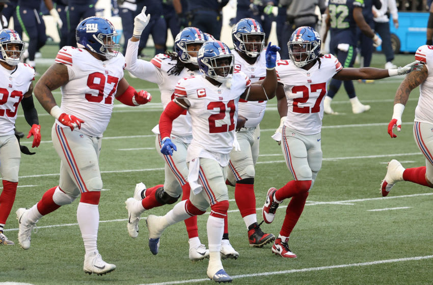 SEATTLE, WASHINGTON - DECEMBER 06: Dexter Lawrence #97, Jabrill Peppers #21 and Isaac Yiadom #27 of the New York Giants celebrate an interception by Darnay Holmes #30 (not pictured) against the Seattle Seahawks during the fourth quarter in the game at Lumen Field on December 06, 2020 in Seattle, Washington. (Photo by Abbie Parr/Getty Images)
