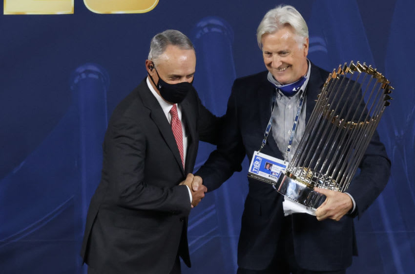 ARLINGTON, TEXAS - OCTOBER 27: MLB Commissioner Rob Manfred presents the Commissioner's Trophy to owner Mark Walter of the Los Angeles Dodgers after their 3-1 win against the Tampa Bay Rays in Game Six to win the 2020 MLB World Series at Globe Life Field on October 27, 2020 in Arlington, Texas. (Photo by Maxx Wolfson/Getty Images)