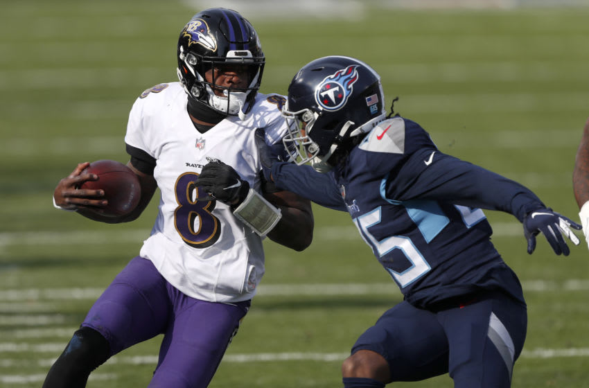 NASHVILLE, TENNESSEE - JANUARY 10: Quarterback Lamar Jackson #8 of the Baltimore Ravens looks to break a tackle from cornerback Adoree' Jackson #25 of the Tennessee Titans during the third quarter of their AFC Wild Card Playoff game at Nissan Stadium on January 10, 2021 in Nashville, Tennessee. (Photo by Wesley Hitt/Getty Images)