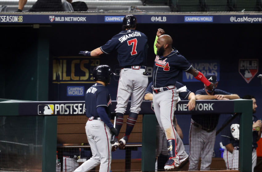 ARLINGTON, TEXAS - OCTOBER 18: Dansby Swanson #7 of the Atlanta Braves is congratulated by Marcell Ozuna #20 after hitting a solo home run against the Los Angeles Dodgers during the second inning in Game Seven of the National League Championship Series at Globe Life Field on October 18, 2020 in Arlington, Texas. (Photo by Tom Pennington/Getty Images)