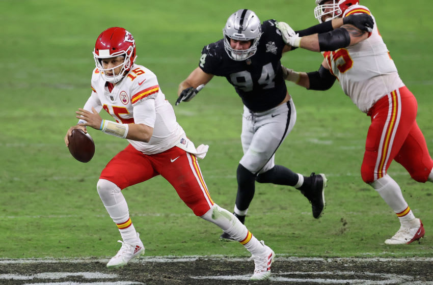 LAS VEGAS, NEVADA - NOVEMBER 22: Quarterback Patrick Mahomes #15 of the Kansas City Chiefs scrambles with the ball past defensive end Carl Nassib #94 of the Las Vegas Raiders during the NFL game at Allegiant Stadium on November 22, 2020 in Las Vegas, Nevada. The Chiefs defeated the Raiders 35-31. (Photo by Christian Petersen/Getty Images)