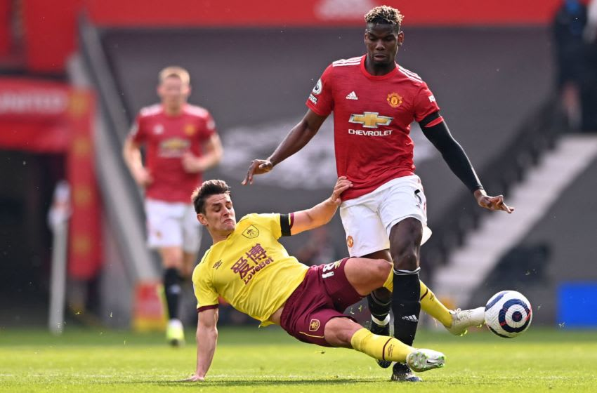 Burnley's English midfielder Ashley Westwood (L) tackles Manchester United's French midfielder Paul Pogba (R) during the English Premier League football match between Manchester United and Burnley at Old Trafford in Manchester, north west England, on April 18, 2021. - RESTRICTED TO EDITORIAL USE. No use with unauthorized audio, video, data, fixture lists, club/league logos or 'live' services. Online in-match use limited to 120 images. An additional 40 images may be used in extra time. No video emulation. Social media in-match use limited to 120 images. An additional 40 images may be used in extra time. No use in betting publications, games or single club/league/player publications. (Photo by STU FORSTER / POOL / AFP) / RESTRICTED TO EDITORIAL USE. No use with unauthorized audio, video, data, fixture lists, club/league logos or 'live' services. Online in-match use limited to 120 images. An additional 40 images may be used in extra time. No video emulation. Social media in-match use limited to 120 images. An additional 40 images may be used in extra time. No use in betting publications, games or single club/league/player publications. / RESTRICTED TO EDITORIAL USE. No use with unauthorized audio, video, data, fixture lists, club/league logos or 'live' services. Online in-match use limited to 120 images. An additional 40 images may be used in extra time. No video emulation. Social media in-match use limited to 120 images. An additional 40 images may be used in extra time. No use in betting publications, games or single club/league/player publications. (Photo by STU FORSTER/POOL/AFP via Getty Images)