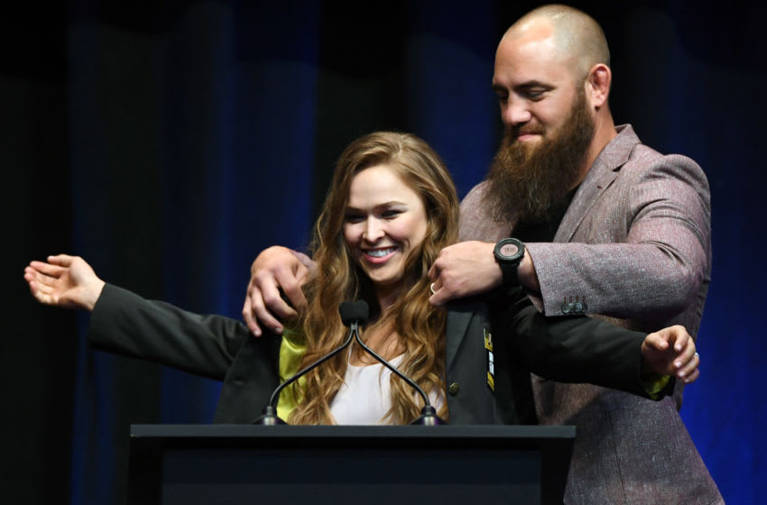 LAS VEGAS, NV - JULY 05: Mixed martial artist Travis Browne (R) puts a UFC Hall of Fame jacket on his wife Ronda Rousey after she became the first female inducted into the UFC Hall of Fame at The Pearl concert theater at Palms Casino Resort on July 5, 2018 in Las Vegas, Nevada. (Photo by Ethan Miller/Getty Images)