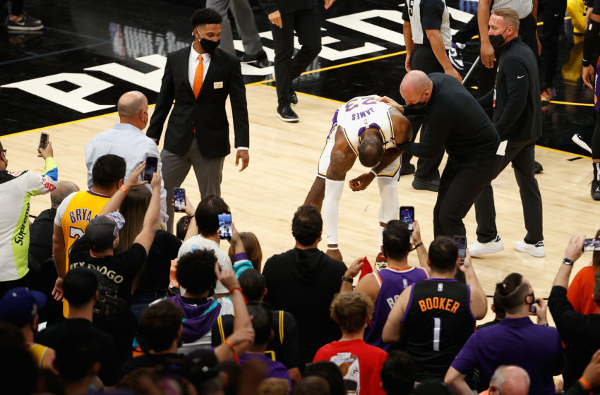 PHOENIX, ARIZONA - MAY 23: LeBron James #23 of the Los Angeles Lakers is helped up by assistant coach Jason Kidd during the second half of Game One of the Western Conference first-round playoff series against the Phoenix Suns at Phoenix Suns Arena on May 23, 2021 in Phoenix, Arizona. NOTE TO USER: User expressly acknowledges and agrees that, by downloading and or using this photograph, User is consenting to the terms and conditions of the Getty Images License Agreement. (Photo by Christian Petersen/Getty Images)
