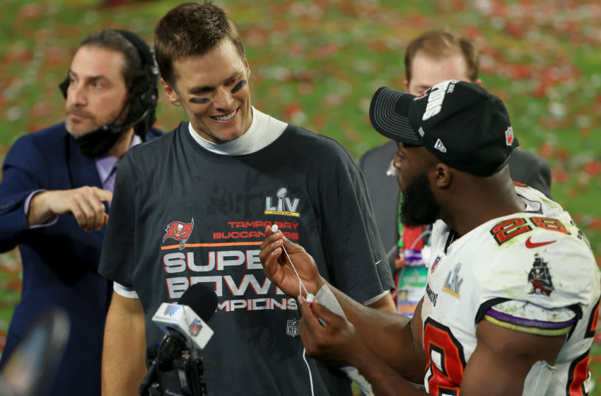 TAMPA, FLORIDA - FEBRUARY 07: Tom Brady #12 of the Tampa Bay Buccaneers is interviewed with Leonard Fournette #28 after winning Super Bowl LV at Raymond James Stadium on February 07, 2021 in Tampa, Florida. The Buccaneers defeated the Chiefs 31-9. (Photo by Mike Ehrmann/Getty Images)