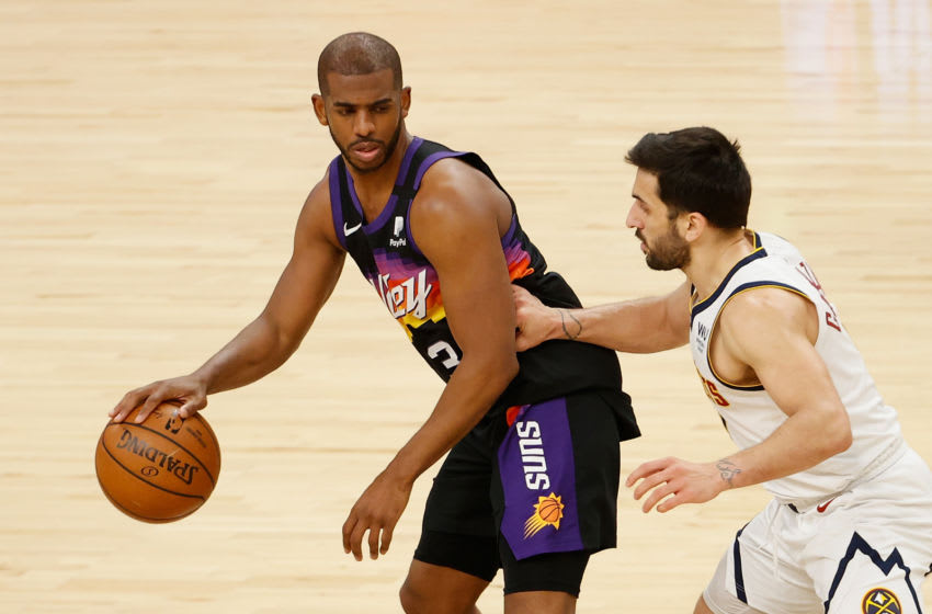 PHOENIX, ARIZONA - JUNE 07: Chris Paul #3 of the Phoenix Suns handles the ball against Facundo Campazzo #7 of the Denver Nuggets during the second half in Game One of the Western Conference second-round playoff series at Phoenix Suns Arena on June 07, 2021 in Phoenix, Arizona. The Suns defeated the Nuggets 122-105. NOTE TO USER: User expressly acknowledges and agrees that, by downloading and or using this photograph, User is consenting to the terms and conditions of the Getty Images License Agreement. (Photo by Christian Petersen/Getty Images)