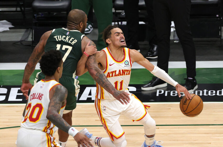 MILWAUKEE, WISCONSIN - JUNE 23: Trae Young #11 of the Atlanta Hawks is fouled by P.J. Tucker #17 of the Milwaukee Bucks during the fourth quarter in game one of the Eastern Conference Finals at Fiserv Forum on June 23, 2021 in Milwaukee, Wisconsin. (Photo by Stacy Revere/Getty Images)