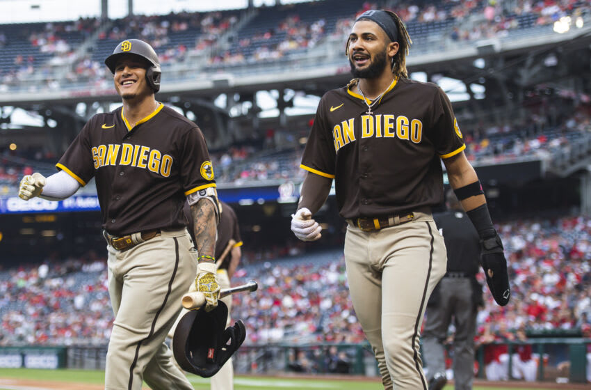 WASHINGTON, D.C. - JULY 17: Fernando Tatis Jr. #23 celebrates with Manny Machado #13 of the San Diego Padres after sliding into home plate and scoring in the first inning against the Washington Nationals at Nationals Park on July 17, 2021 in Washington, DC. (Photo by Matt Thomas/San Diego Padres/Getty Images)