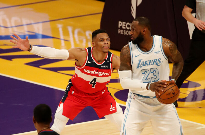 LOS ANGELES, CALIFORNIA - FEBRUARY 22: Russell Westbrook #4 of the Washington Wizards guards LeBron James #23 of the Los Angeles Lakers during the fourth quarter at Staples Center on February 22, 2021 in Los Angeles, California. NOTE TO USER: User expressly acknowledges and agrees that, by downloading and or using this photograph, User is consenting to the terms and conditions of the Getty Images License Agreement. (Photo by Katelyn Mulcahy/Getty Images)
