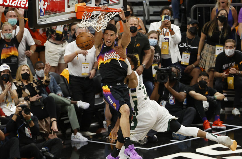PHOENIX, ARIZONA - JULY 17: Giannis Antetokounmpo #34 of the Milwaukee Bucks fouls Devin Booker #1 of the Phoenix Suns during the first half in Game Five of the NBA Finals at Footprint Center on July 17, 2021 in Phoenix, Arizona. NOTE TO USER: User expressly acknowledges and agrees that, by downloading and or using this photograph, User is consenting to the terms and conditions of the Getty Images License Agreement. (Photo by Christian Petersen/Getty Images)