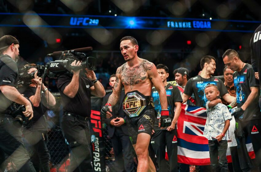 Jul 27, 2019; Edmonton, Alberta, Canada; Max Holloway (red gloves) defeats Frankie Edgar (blue gloves) during UFC 240 at Rogers Place. Mandatory Credit: Sergei Belski-USA TODAY Sports