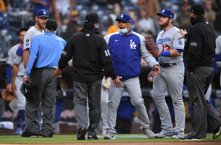 Apr 17, 2021; San Diego, California, USA; Los Angeles Dodgers manager Dave Roberts (third from right) talks to first base umpire Phil Cuzzi (10) before a replay review during the fourth inning at Petco Park. Mandatory Credit: Orlando Ramirez-USA TODAY Sports