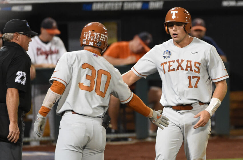 Jun 24, 2021; Omaha, Nebraska, USA; Texas Longhorns designated hitter Ivan Melendez (17) celebrates with outfielder Eric Kennedy (30) after scoring a run during the second inning against the Virginia Cavaliers at TD Ameritrade Park. Mandatory Credit: Steven Branscombe-USA TODAY Sports