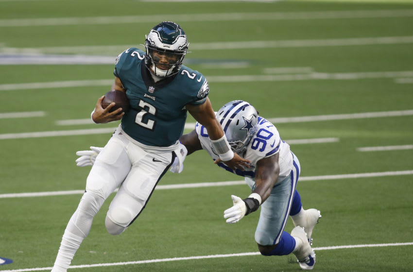 Dec 27, 2020; Arlington, Texas, USA; Philadelphia Eagles quarterback Jalen Hurts (2) runs the ball against Dallas Cowboys defensive end DeMarcus Lawrence (90) in the first quarter at AT&T Stadium. Mandatory Credit: Tim Heitman-USA TODAY Sports