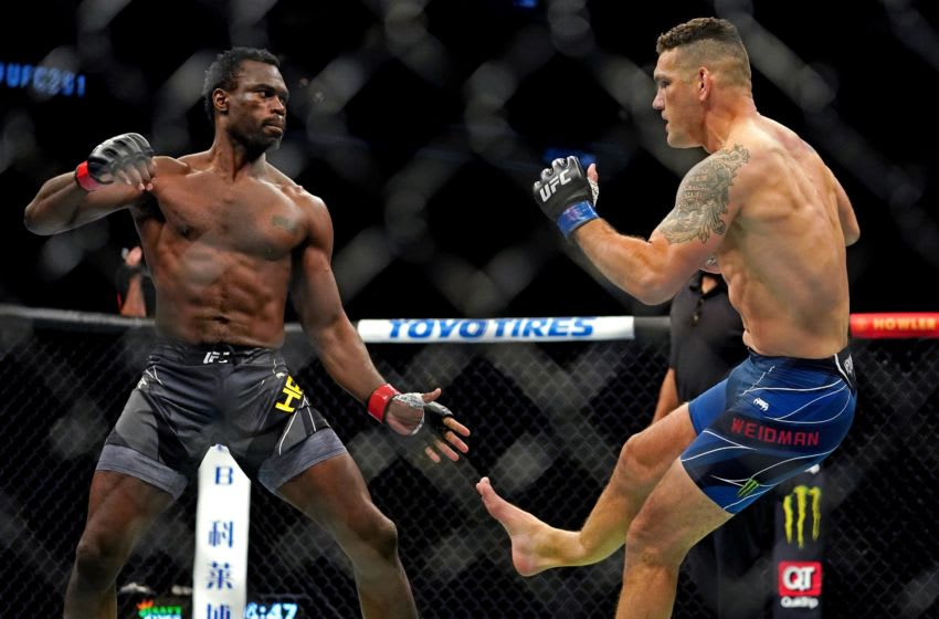 Apr 24, 2021; Jacksonville, Florida, USA; Chris Weidman (Blue Gloves) breaks his leg on a kick to the legs of Uriah Hall (Red Gloves) during UFC 261 at VyStar Veterans Memorial Arena. Mandatory Credit: Jasen Vinlove-USA TODAY Sports