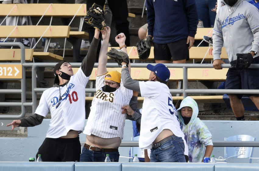 Apr 25, 2021; Los Angeles, California, USA; A San Diego Padres fan reaches up to vie for a home run hit by Los Angeles Dodgers second baseman Chris Taylor (3) between two Dodger fans during the sixth inning at Dodger Stadium. Mandatory Credit: Kelvin Kuo-USA TODAY Sports