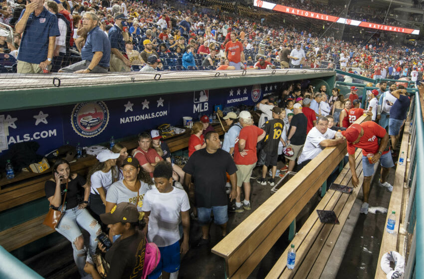Jul 17, 2021; Washington, District of Columbia, USA; Fans take cover in the San Diego Padres dugout after apparent gun shots were heard during the game between the Washington Nationals and the San Diego Padres at Nationals Park. Mandatory Credit: Brad Mills-USA TODAY Sports