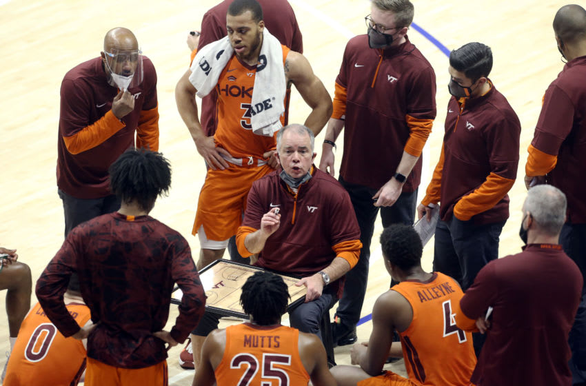 Feb 3, 2021; Pittsburgh, Pennsylvania, USA; Virginia Tech Hokies head coach Mike Young (center) talks to the Hokies during a time-out against the Pittsburgh Panthers in the first half at the Petersen Events Center. Mandatory Credit: Charles LeClaire-USA TODAY Sports