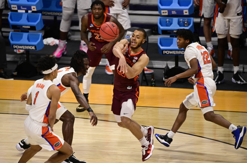 Mar 19, 2021; Indianapolis, Indiana, USA; Virginia Tech Hokies guard Wabissa Bede (middle) passes the ball as Florida Gators guard Tre Mann (1) looks on during the first round of the 2021 NCAA Tournament at Hinkle Fieldhouse. Mandatory Credit: Marc Lebryk-USA TODAY Sports