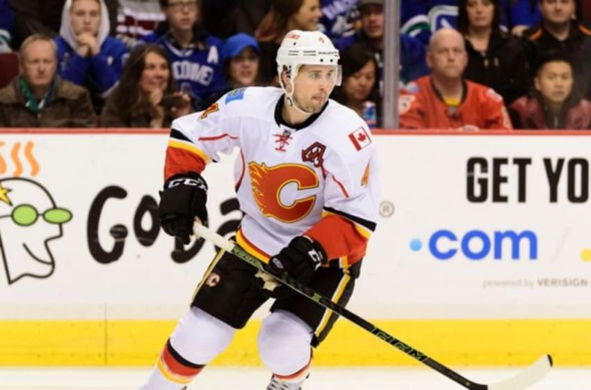 Feb 6, 2016; Vancouver, British Columbia, CAN; Calgary Flames defenseman Kris Russell (4) controls the puck against the Vancouver Canucks during the first period at Rogers Arena. The Calgary Flames won 4-1. Mandatory Credit: Anne-Marie Sorvin-USA TODAY Sports