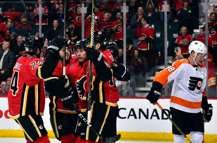 CALGARY, AB - DECEMBER 12: Sam Bennett #93 and Travis Hamonic #24 of the Calgary Flames and teammates celebrate a goal against the Philadelphia Flyers during an NHL game on December 12, 2018 at the Scotiabank Saddledome in Calgary, Alberta, Canada. (Photo by Terence Leung/NHLI via Getty Images)