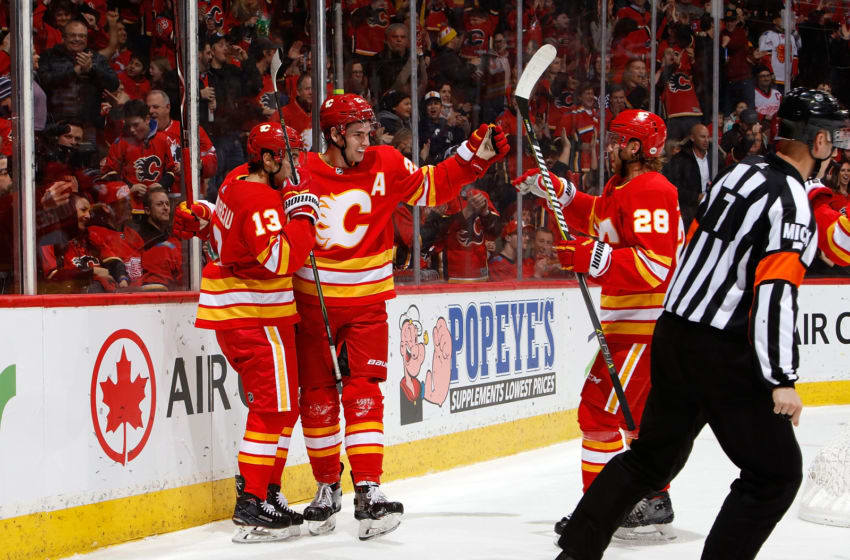 CALGARY, AB - JANUARY 18: Sean Monahan #23, Johnny Gaudreau #13 and teammates of the Calgary Flames celebrate a goal against the Detroit Red Wings during an NHL game on January 18, 2019 at the Scotiabank Saddledome in Calgary, Alberta, Canada. (Photo by Gerry Thomas/NHLI via Getty Images)