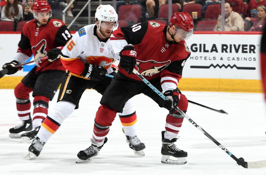 GLENDALE, AZ - MARCH 07: Michael Grabner #40 of the Arizona Coyotes plays the puck in front of Noah Hanifin #55 of the Calgary Flames during the second period at Gila River Arena on March 7, 2019 in Glendale, Arizona. (Photo by Norm Hall/NHLI via Getty Images)