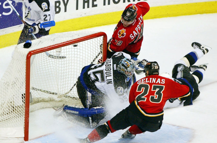 CALGARY, CANADA - JUNE 5: Goaltender Nikolai Khabibulin #35 of the Tampa Bay Lightning stops a puck shot by Martin Gelinas #23 of the Calgary Flames during the third period in game six of the NHL Stanley Cup Finals on June 5, 2004 at the Pengrowth Saddledome in Calgary, Canada. A television replay showed that the puck might have crossed the goal line. (Photo by Jeff Vinnick/Getty Images)