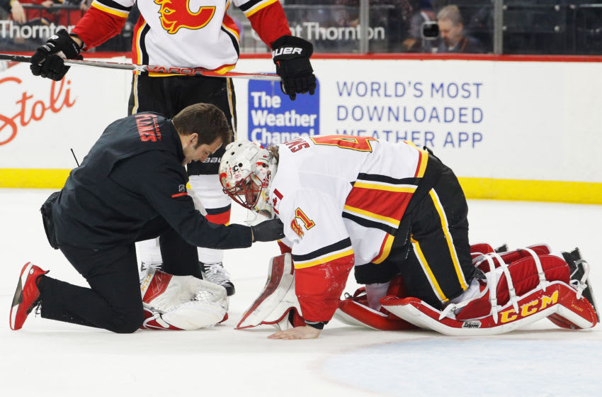 NEW YORK, NY - FEBRUARY 11: A trainer tends to Mike Smith #41 of the Calgary Flames during the final moments of a 3-2 win against the New York Islanders at Barclays Center on February 11, 2018 in the Brooklyn borough of New York City. (Photo by Paul Bereswill/NHLI via Getty Images)
