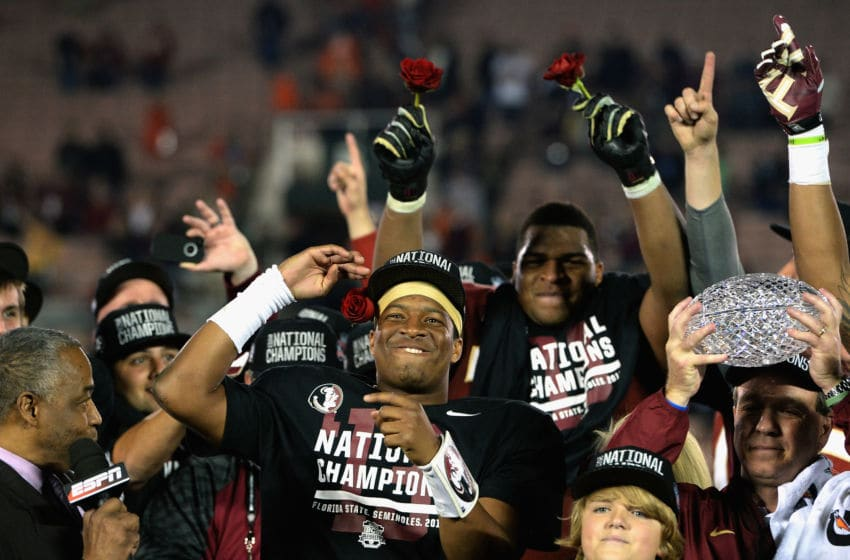 Florida State Seminoles head coach Jimbo Fisher (R) holds the Coaches' Trophy as quarterback Jameis Winston (center) #5 celebrates after defeating the Auburn Tigers 34-31 in the 2014 Vizio BCS National Championship Game at the Rose Bowl on January 6, 2014 in Pasadena, California. (Photo by Harry How/Getty Images)
