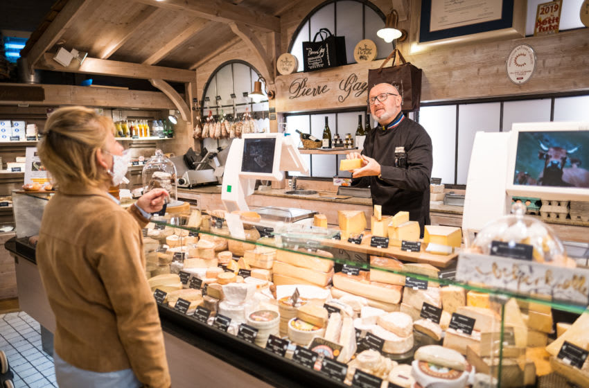 ANNECY, FRANCE - APRIL 16: A woman buy cheese after collecting her basket of fresh vegetables and fruits from 'Le Col Fleuri' farm at Pierre Gay's shop on April 16, 2020 in Annecy, France. During the COVID-19 outbreak and lockdown, Cheesemonger Pierre Gay transforms his shop located downtown Annecy as a relay between a local farm and clients. The Coronavirus (COVID-19) pandemic has spread to many countries across the world, claiming over 130,000 lives and infecting over 2 million people. (Photo by Richard Bord/Getty Images)