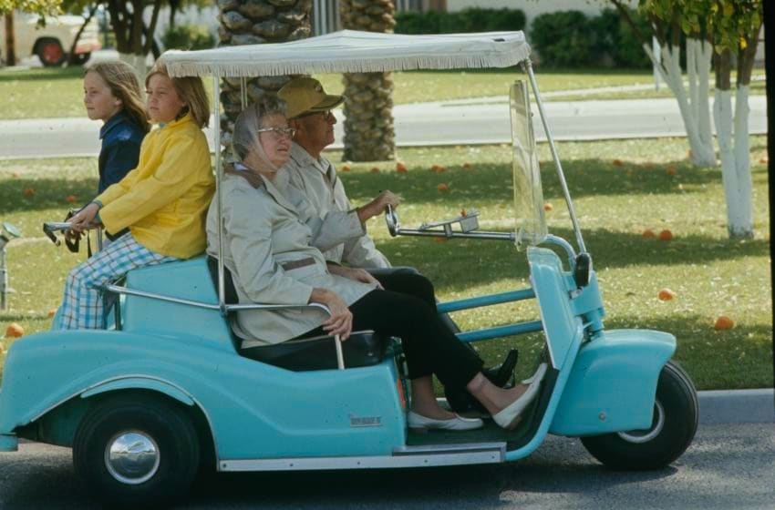 An older man and woman with two children driving a golf cart around Sun City, a planned retirement village in Arizona, in 1970. (Photo by Ralph Crane/The LIFE Picture Collection via Getty Images)