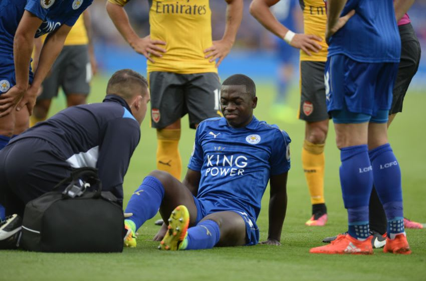 Leicester City's French midfielder Nampalys Mendy (C) receives attention on the pitch for an injury before being substituted during the English Premier League football match between Leicester City and Arsenal at King Power Stadium in Leicester, central England on August 20, 2016. / AFP / OLI SCARFF / RESTRICTED TO EDITORIAL USE. No use with unauthorized audio, video, data, fixture lists, club/league logos or 'live' services. Online in-match use limited to 75 images, no video emulation. No use in betting, games or single club/league/player publications. / (Photo credit should read OLI SCARFF/AFP/Getty Images)
