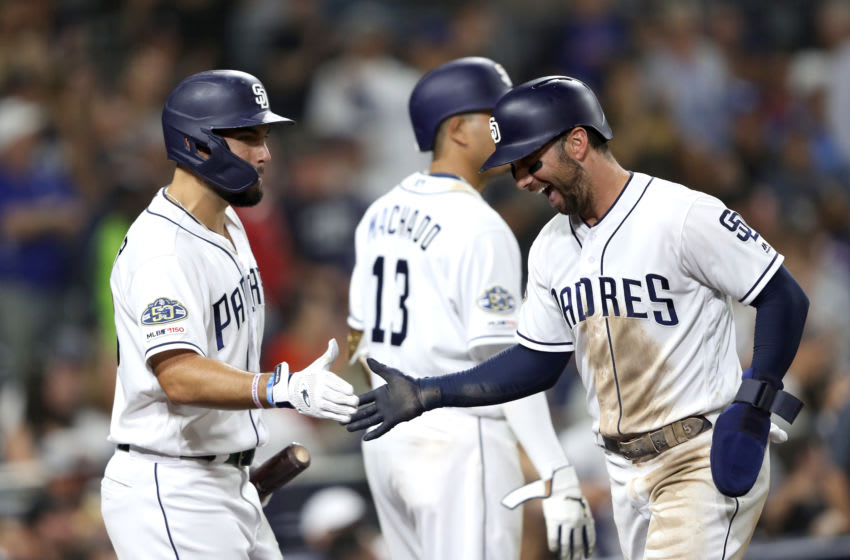 SAN DIEGO, CALIFORNIA - AUGUST 26: Greg Garcia #5 is congratulated by Eric Hosmer #30 of the San Diego Padres after scoring on a throwing error during the sixth inning of a game against the Los Angeles Dodgers at PETCO Park on August 26, 2019 in San Diego, California. (Photo by Sean M. Haffey/Getty Images)
