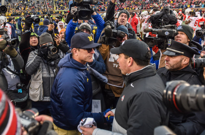 ANN ARBOR, MICHIGAN - NOVEMBER 30: Head Coach Ryan Day (R) of the Ohio State Buckeyes shakes hands with Head Coach Jim Harbaugh (L) of the Michigan Wolverines after a college football game at Michigan Stadium on November 30, 2019 in Ann Arbor, MI. The Ohio State Buckeyes won the game 56-27 over the Michigan Wolverines. (Photo by Aaron J. Thornton/Getty Images)