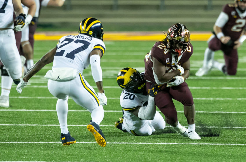 MINNEAPOLIS, MINNESOTA - OCTOBER 24: Mohamed Ibrahim #24 of the Minnesota Golden Gophers is tackled by Brad Hawkins #20 of the Michigan Wolverines while Hunter Reynolds #27 defends in the fourth quarter of the game at TCF Bank Stadium on October 24, 2020 in Minneapolis, Minnesota. The Wolverines defeated the Gophers 49-24. (Photo by David Berding/Getty Images)