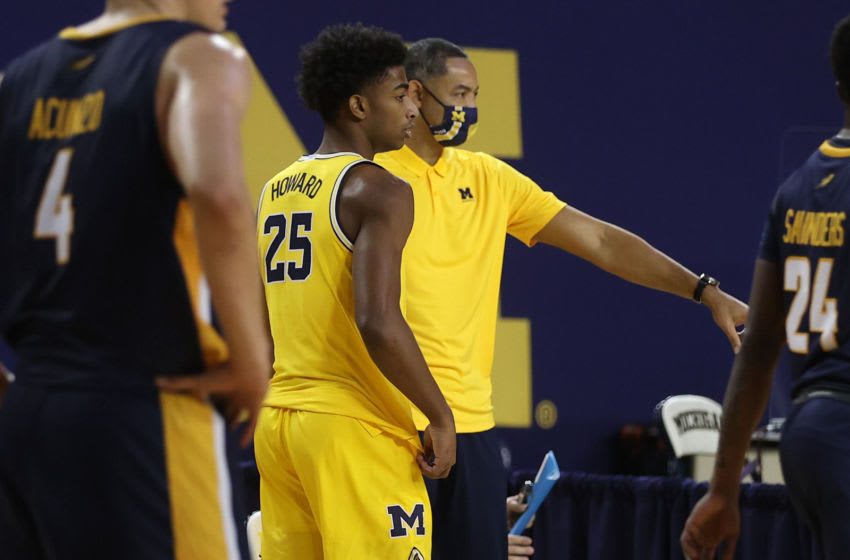 ANN ARBOR, MICHIGAN - DECEMBER 09: Head coach Juwan Howard of the Michigan Wolverines looks on next to his son Jace Howard #25 while playing the Toledo Rockets at Crisler Arena on December 09, 2020 in Ann Arbor, Michigan. (Photo by Gregory Shamus/Getty Images)