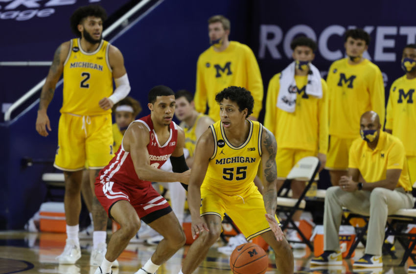 ANN ARBOR, MICHIGAN - JANUARY 12: Eli Brooks #55 of the Michigan Wolverines looks to drive the ball as D'Mitrik Trice #0 of the Wisconsin Badgers defends during the second half of the game at Crisler Arena on January 12, 2021 in Ann Arbor, Michigan. Michigan defeated Wisconsin 77-54. (Photo by Leon Halip/Getty Images)