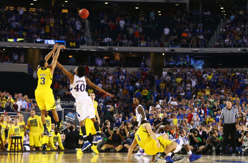 ARLINGTON, TX - MARCH 29: Trey Burke #3 of the Michigan Wolverines shoots a game tying three pointer in the final seconds of the second half over Kevin Young #40 of the Kansas Jayhawks during the South Regional Semifinal round of the 2013 NCAA Men's Basketball Tournament at Dallas Cowboys Stadium on March 29, 2013 in Arlington, Texas. (Photo by Ronald Martinez/Getty Images)