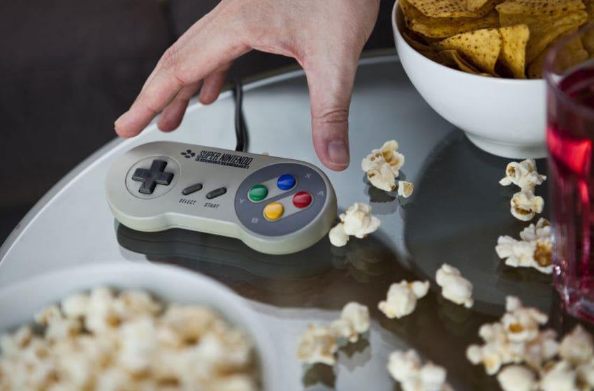 Detail of a hand picking up a vintage Nintendo SNES controller from a glass table, surrounded by bowls of snacks, taken on July 9, 2013. (Photo by Philip Sowels/Future Publishing via Getty Images)