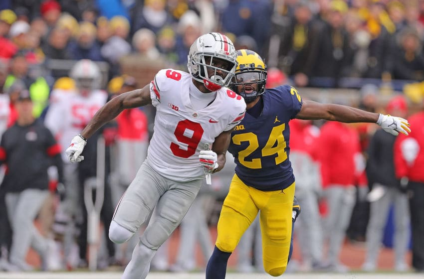 ANN ARBOR, MI - NOVEMBER 30: Binjimen Victor #9 of the Ohio State Buckeyes and Lavert Hill #24 of the Michigan Wolverines battle during the first quarter of the game at Michigan Stadium on November 30, 2019 in Ann Arbor, Michigan. Ohio State defeated Michigan 56-27. (Photo by Leon Halip/Getty Images)