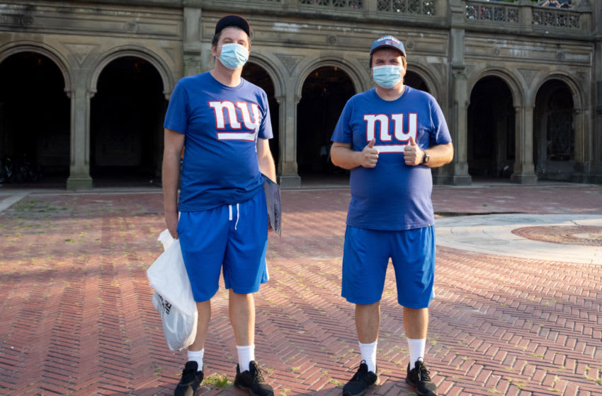 NEW YORK, NEW YORK - JULY 31: Two men wearing masks are dressed in matching NY Giants outfits in Central Park as the city continues Phase 4 of re-opening following restrictions imposed to slow the spread of coronavirus on July 31, 2020 in New York City. The fourth phase allows outdoor arts and entertainment, sporting events without fans and media production. (Photo by Alexi Rosenfeld/Getty Images)