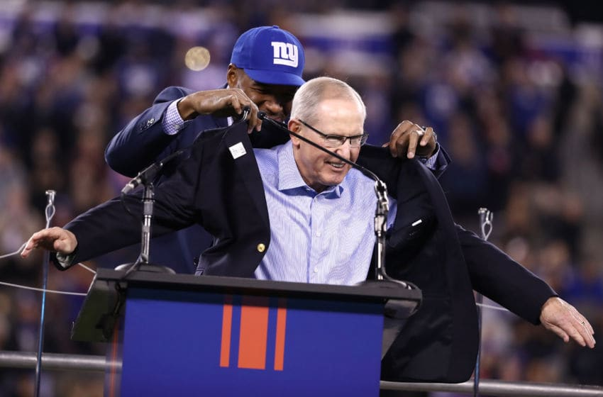 EAST RUTHERFORD, NJ - NOVEMBER 14: Former Defensive End Michael Strahan puts a coat on 2016 Giants Ring of Honor Inductee Tom Coughlin during the halftime ceremony of the game between the Cincinnati Bengals and the New York Giants at MetLife Stadium on November 14, 2016 in East Rutherford, New Jersey. (Photo by Al Bello/Getty Images)