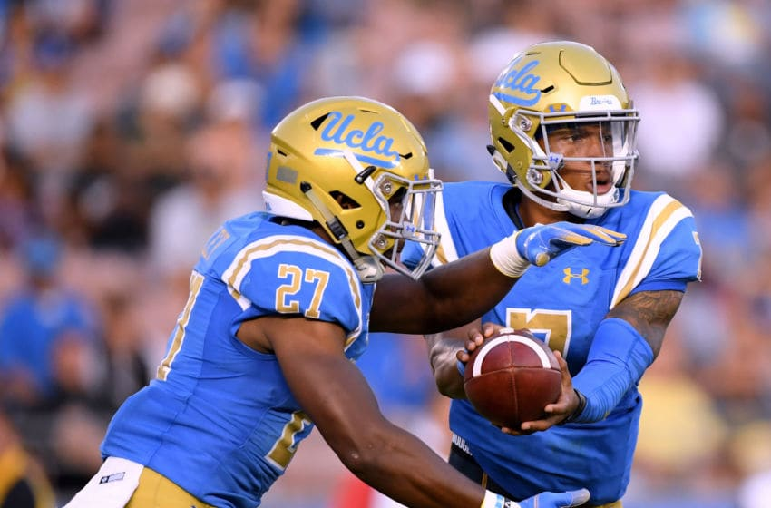 PASADENA, CA - SEPTEMBER 01: Dorian Thompson-Robinson #7 of the UCLA Bruins hands off to Joshua Kelley #27 during a 26-17 loss to the Cincinnati Bearcats at Rose Bowl on September 1, 2018 in Pasadena, California. (Photo by Harry How/Getty Images)