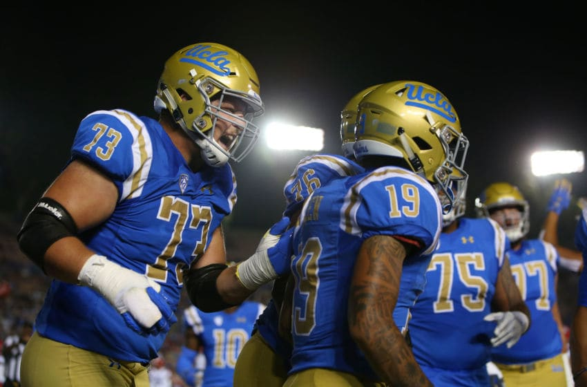 PASADENA, CA - OCTOBER 20: Offensive lineman Jake Burton #73 of the UCLA Bruins shouts in celebration at teammate Kazmeir Allen #19 after Allen's touchdown during the first half of the NCAA college football game against the Arizona Wildcats at the Rose Bowl on October 20, 2018 in Pasadena, California. The Bruins defeated the Wildcats 31-30. (Photo by Victor Decolongon/Getty Images)